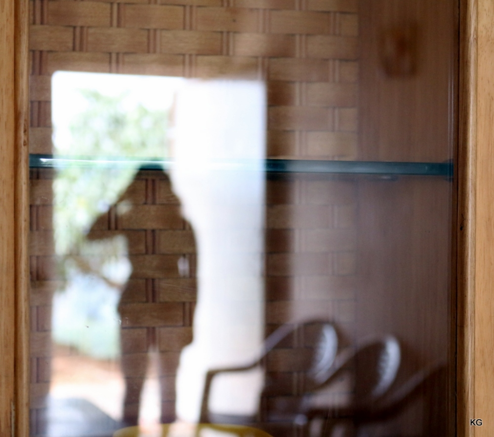 For a change, a woman walking through the door captured in a glass